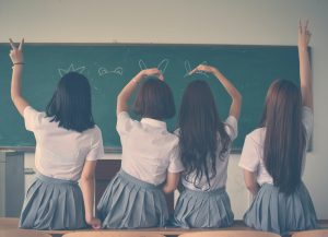 four girls in a classroom making hand signs to the board