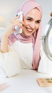 woman in pink hijab holding phone