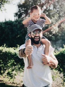 man holding his son and giving thumbs up